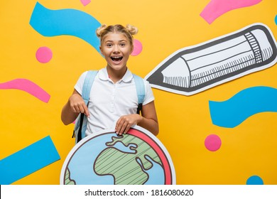 joyful schoolkid pointing with finger at globe maquette near paper pencil and multicolored elements on yellow