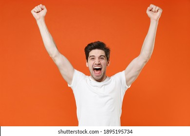 Joyful screaming young man 20s in basic casual white blank empty t-shirt standing clenching fists doing winner gesture looking camera isolated on bright orange colour wall background, studio portrait