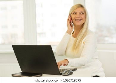 Joyful senior attractive businesswoman smiling happily talking on the phone while working on her laptop copyspace technology mobility communication online multitasking social media startup leader.