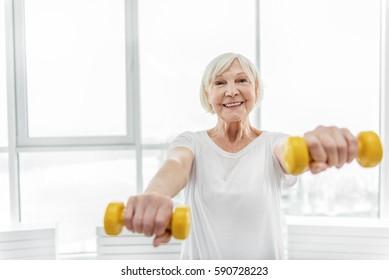 Joyful senior lady exercising with weights