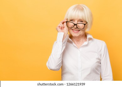 Joyful senior lady in glasses laughing isolated over yellow background. Friendly, mature white haired woman wearing glasses with a smile.