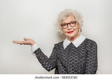 Joyful senior lady showing something by her arm
