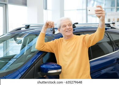 Joyful senior man smiling taking a selfie with car keys to his new auto using his smart phone at the dealership showroom technology social media news sharing offer discount rental people positivity