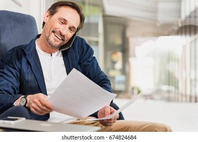 Joyful senior man speaking by cellphone on workplace