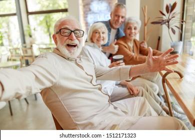 Joyful senior man spending time with friends stock photo