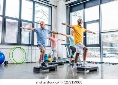 joyful senior multicultural athletes synchronous exercising on step platforms at gym