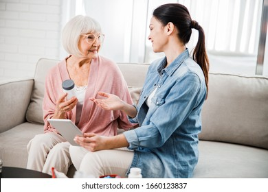 Joyful senior woman holding bottle of vitamins while talking with family physician at home stock photo