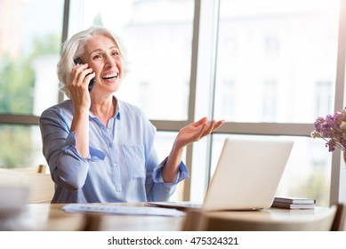Joyful senior woman sitting at the table