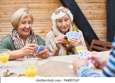 Joyful senior women wearing warm clothes playing poker with friends while sitting at outdoor cafe table