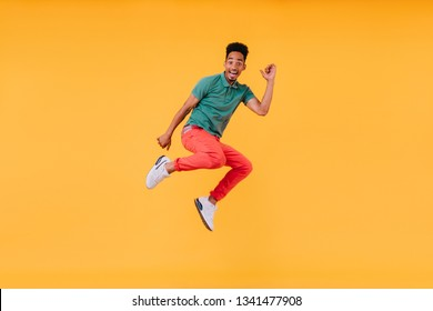 Joyful short-haired guy jumping on yellow background. Indoor photo of stunning male model in green t-shirt having fun in studio.