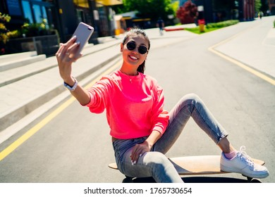 Joyful skater dressed in fashionable streetwear clicking content selfie during leisure in city, sincerely hipster girl sitting at longboard and creating influence vlog for sharing to social networks