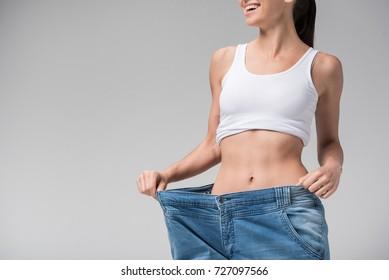 Joyful slim girl showing result of diet