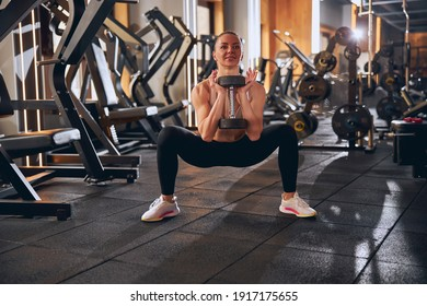 Joyful slim strong woman is using heavy dumbbell for buttocks training during deep goblet squats