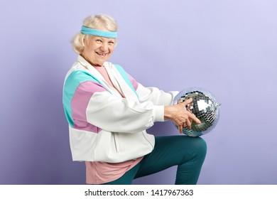 Joyful smiling aged woman portrait dressed in sportswear, holding mirrow ball, set in purple studio. Age of health, leisure, entertainment in retirement