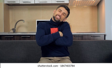 Joyful smiling bearded man sits on couch at home hugs red box rejoices gift. Handsome male in blue sweater with gift in hands on background kitchen