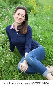 Joyful smiling beautiful woman sitting green grass on summer field