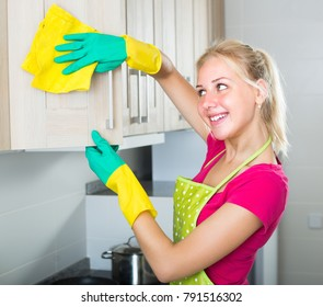 joyful smiling blonde girl wearing protective gloves and apron and cleaning in apartment