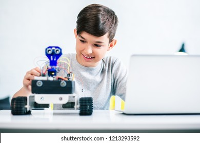Joyful smiling boy trying up robot while preparing for engineering classes at home