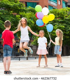joyful smiling children in elementary school age playing with chinese jumping rope at playground  . Selective focus