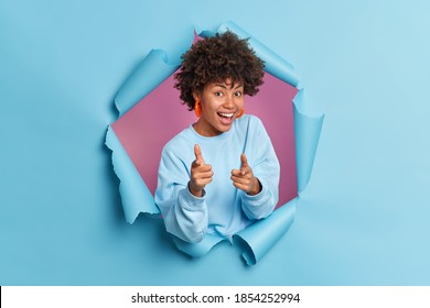 Joyful smiling dark skinned Afro American woman points index fingers at camera makes gun gesture picks you selects someone dressed in casual blue jumper stands through paper torn hole. Join me