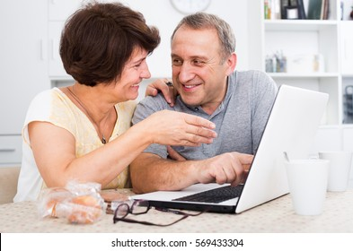 joyful smiling elderly couple looking on laptop screen  indoors at home together