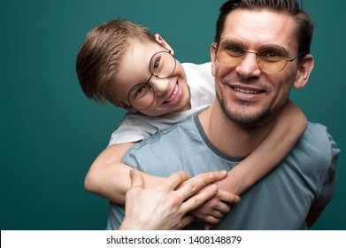 Joyful smiling father and his little kid wearing casual t-shirts and stylish spectacles hugging. Happy Father's Day