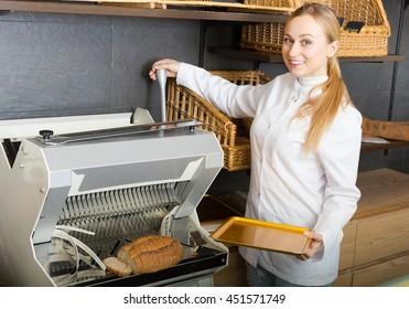 Joyful smiling girl baker cutting bread on the bread-slicer machine