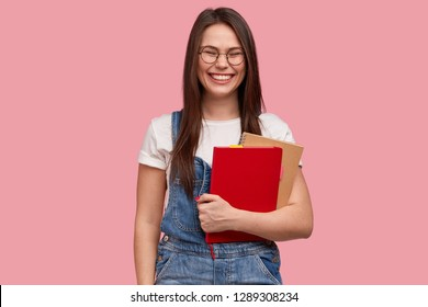 Joyful smiling teenage girl with pleased expression, carries two textbooks, has toothy smile, laughs at something good, wears casual clothes, stands over pink studio background. Studying concept