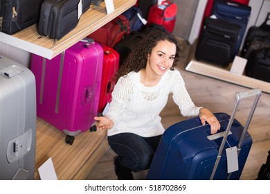 Joyful smiling young brunette selecting handy trunk in store