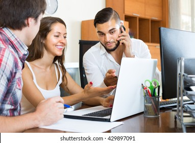 Joyful smiling young colleagues watching something on laptop in the office