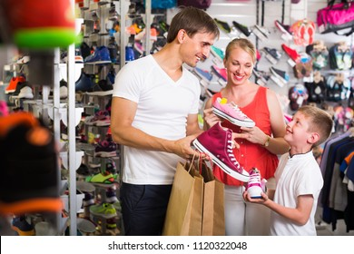 joyful smiling young parents with boy choosing new sport shoes in sport shop. Fccosu on man