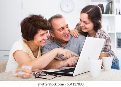 joyful smiling young woman helping her elderly parents to learn how to use laptop at home