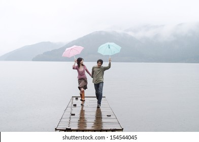 Joyful and spontaneous japanese couple in love, holding hands and running on a wooden pier on a natural lake and mountains landscape, having fun and laughing outdoors.