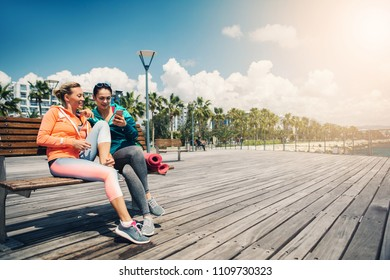 Joyful sportswomen are chatting after workout. They are looking cellphone and smiling while relaxing near the sea