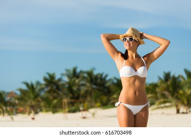 Joyful tanned woman in white bikini having fun at tropical beach during travel vacation to Mayan Riviera, Mexico.