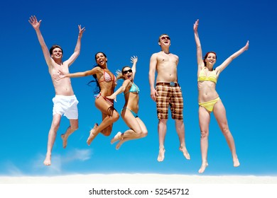 Joyful team of friends holding each other by hands and jumping