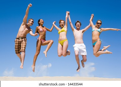Joyful team of friends holding for hands each other and jumping
