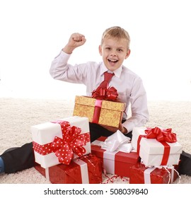 joyful teenager boy with his hand raised in a gesture of victory with boxes of gifts in a white shirt and red tie