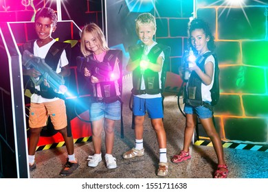 Joyful teens aiming laser guns at other players during lasertag game in dark room