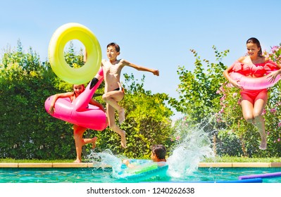 Joyful teens jumping into water with pool toys