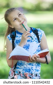 Joyful thoughtful Caucasian girl stands in summer park with sketchpad and color pencil in hands, portrait