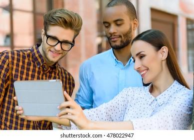 Joyful three colleagues using modern gadget