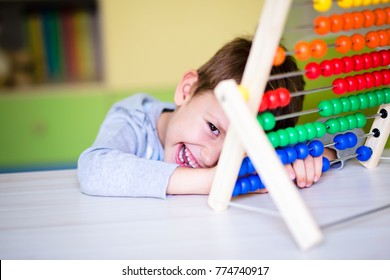 Joyful toddler boy learning to count using the abacus. Early kids development. Preschool at home.