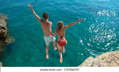 Joyful tourist couple decides to jump off a rocky cliff and dive into sea. Unrecognizable man holds his gorgeous girlfriend's hand while diving into the refreshing blue sea on a sunny summer day.