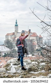 Joyful tourist woman is photographing with Mikulov castle, southern Moravia, Czech republic. Travel destination.