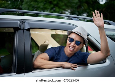 Joyful Vietnamese man wearing hat and sunglasses sitting in car and waving out of window, head and shoulders portrait