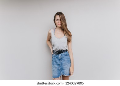 Joyful white woman in denim skirt relaxing during indoor photoshoot. Studio portrait of beautiful european girl isolated on light background with pretty smile.