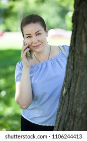 Joyful woman in blue blouse communicates by smartphone standing near tree, looking at camera