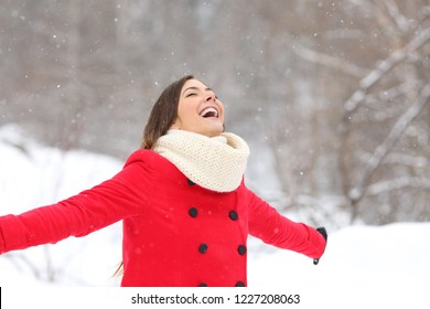 Joyful woman breathing fresh air enjoying snow in a snowy mountain