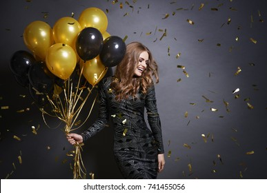 Joyful woman with bunch of balloons